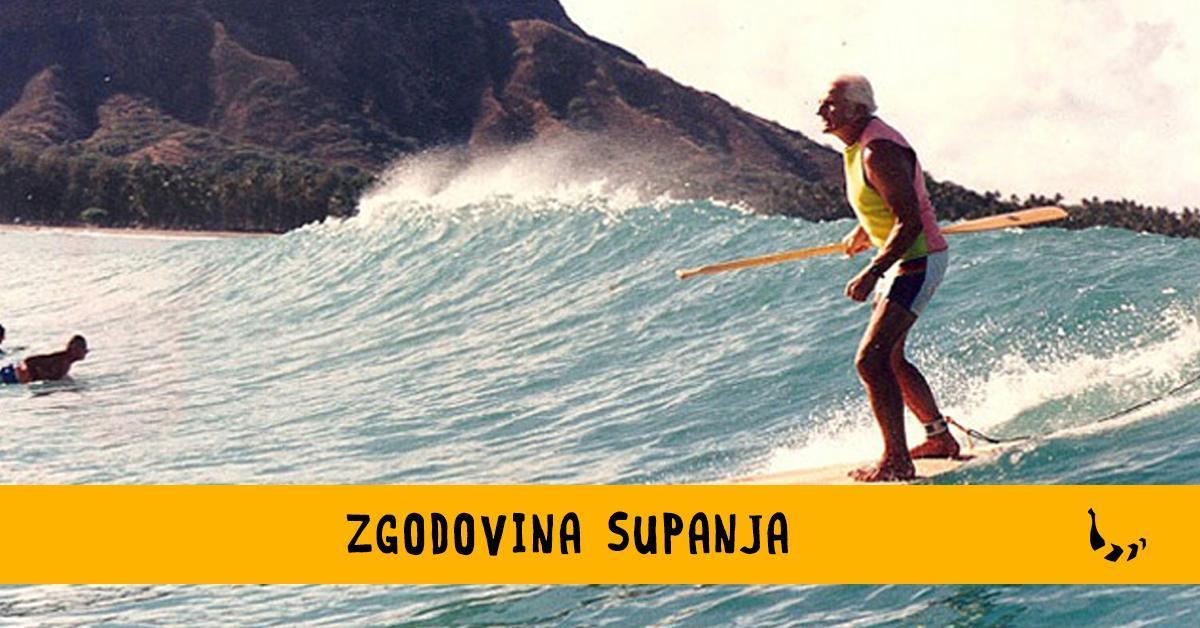 Starejši moški z veslom v roki stoji na deski, s katero surfa po valovih