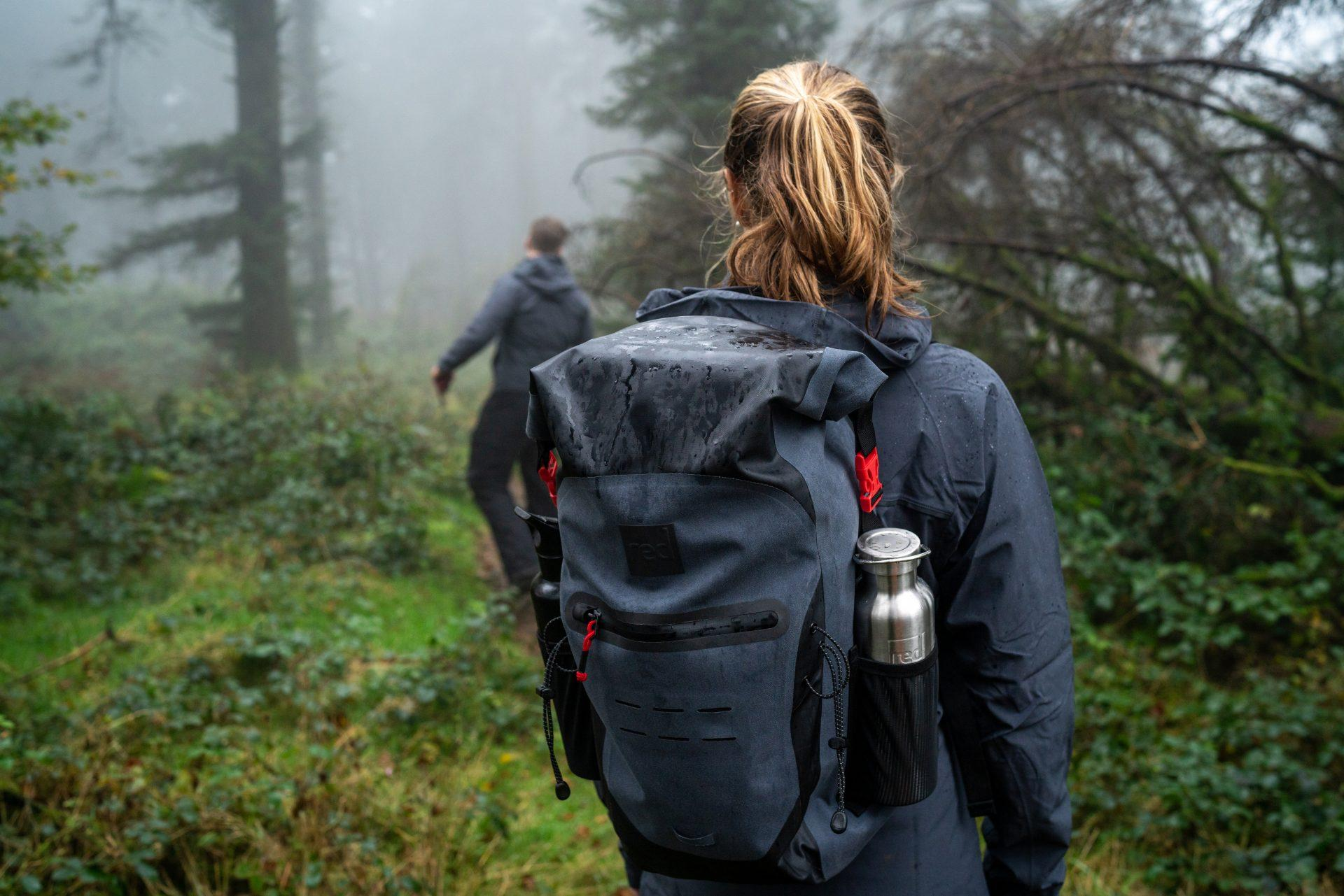 Dekle z vodoodpornim nahrbrtnikom 30L Red Original na pohodu v gozdu