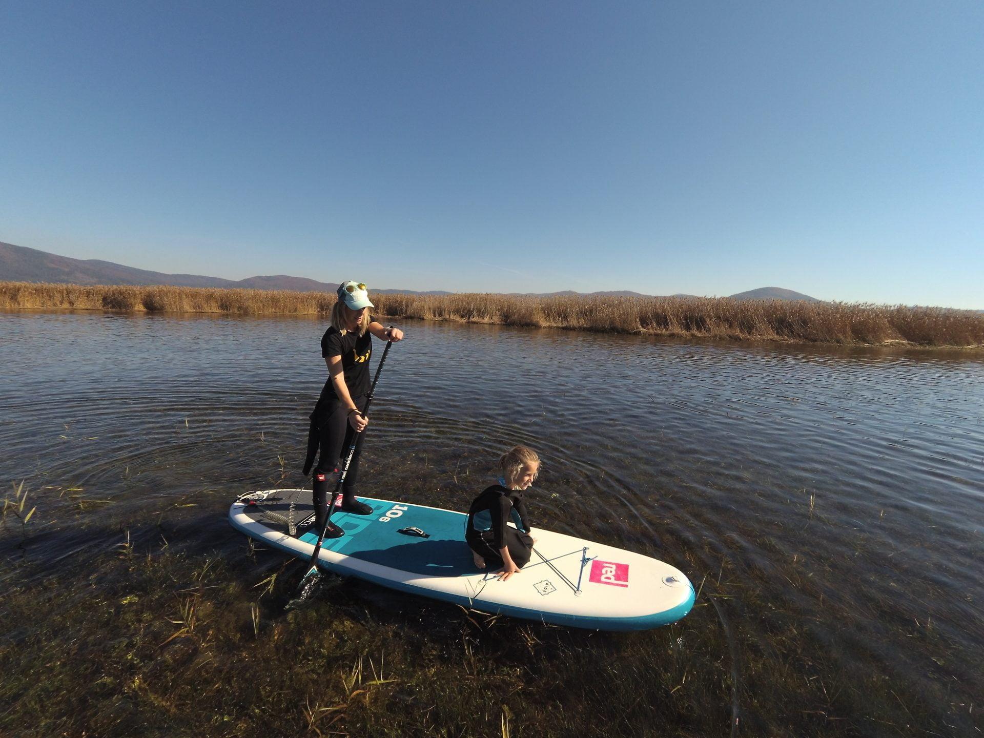 Suparka z otrokom, ki sedi spredaj na supu na Cerkniškem jezeru