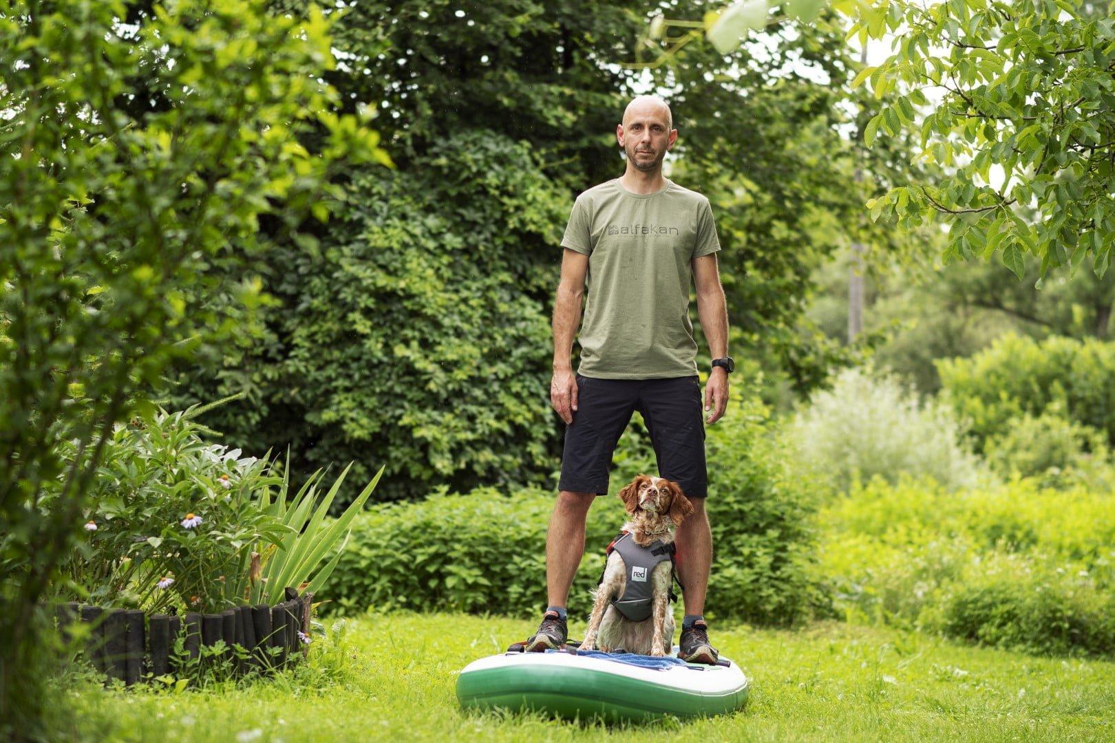 Andrej in psička Fija stojina na supu na travi, se navajata na sup